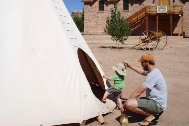 Father helping child to get into a teepee at Bluff Fort